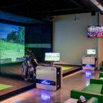 Image of simulator bays and computers at X-Golf