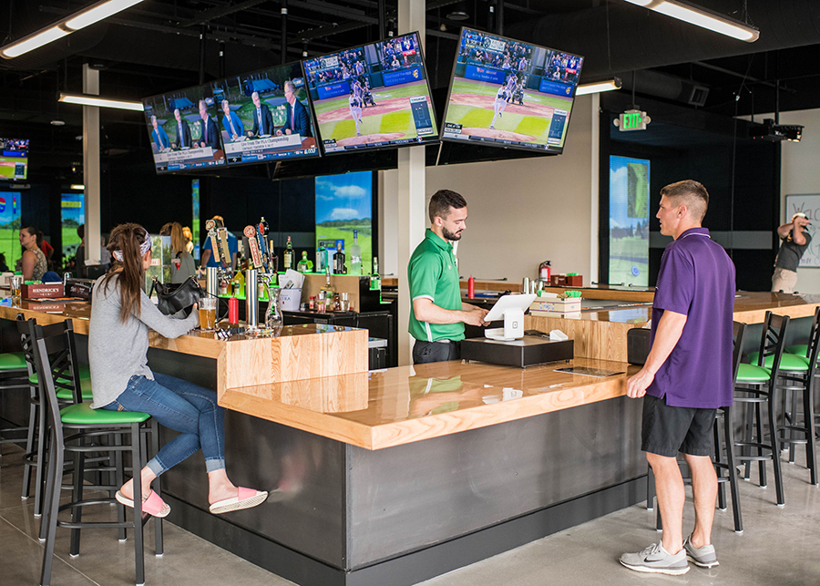Image of woman watching sports while man orders a drink at X-Golf