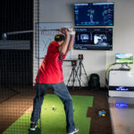 Image of man in jeans hitting at X-Golf