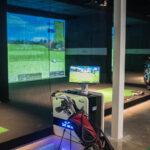 Image of X-Golf computer and simulator bays behind a golf bag