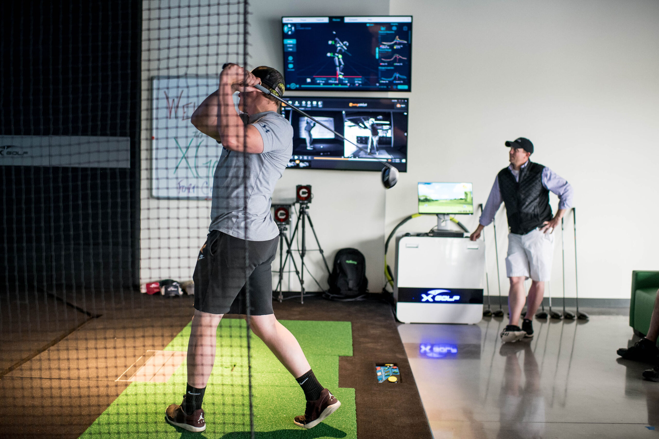 Image of man watching his friend hit at X-Golf