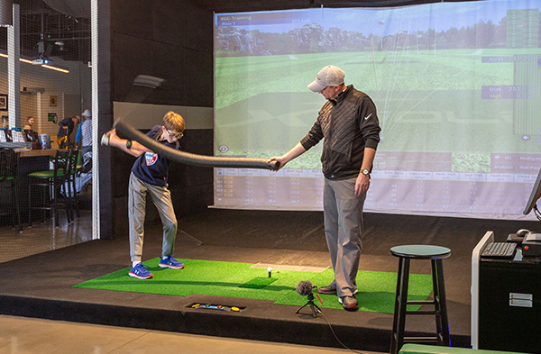 Far image of golf pro helping young boy with his swing